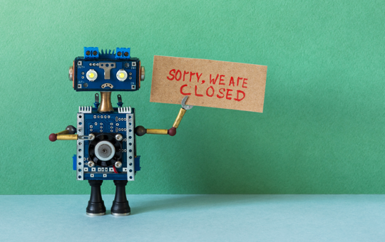 A robot holding a sign saying sorry were closed